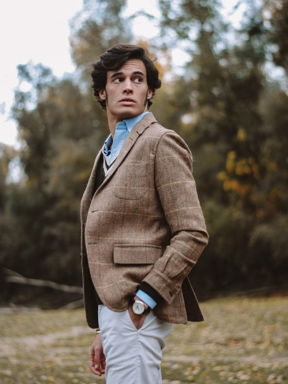 Dario con teba oliva y jersey ivy league con arboles de fondo
